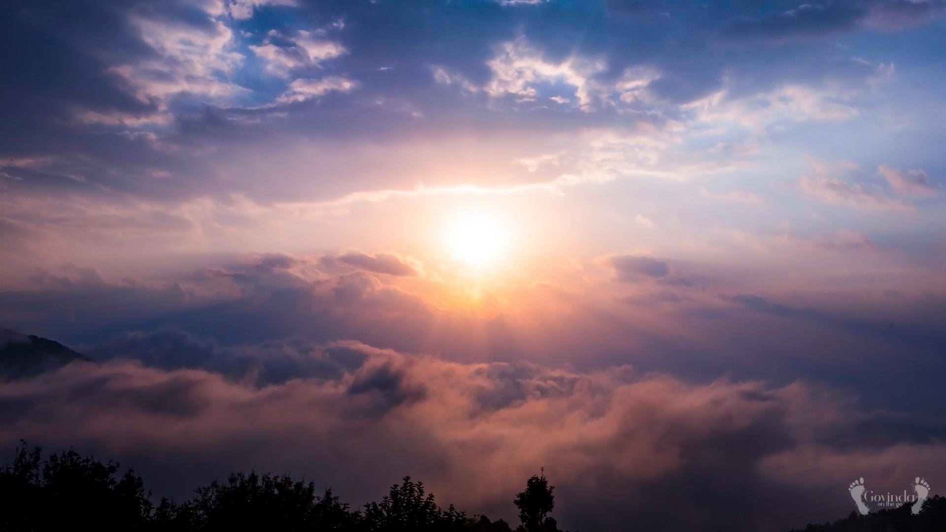 Sun penetrating cloudy sky in Himalayas